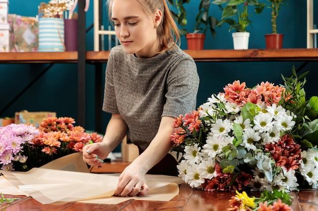 Kwiaciarnia robi bukiet. młoda dorosła dziewczyna wybiera papier do dekoracji.