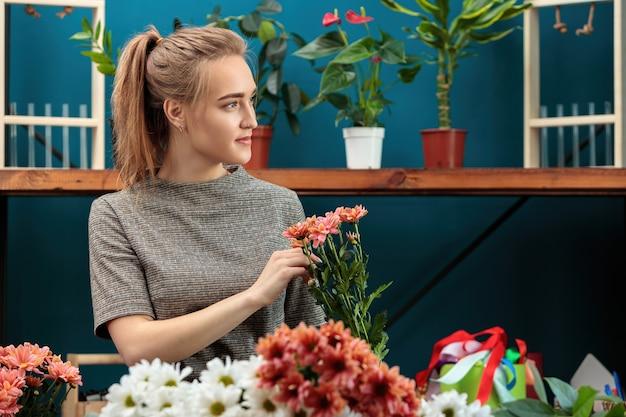Kwiaciarnia robi bukiet wielokolorowych chryzantem. młoda dorosła dziewczyna patrzy w bok.