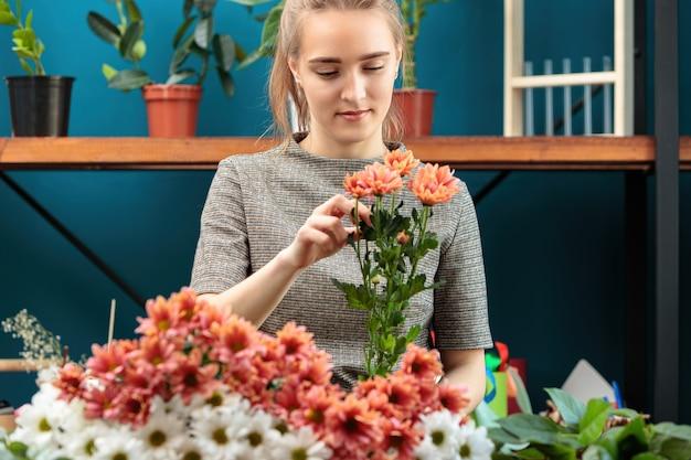 Kwiaciarnia robi bukiet wielokolorowych chryzantem. młoda dorosła dziewczyna pracuje z entuzjazmem.