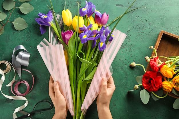 Kwiaciarnia robi piękny bukiet przy stole