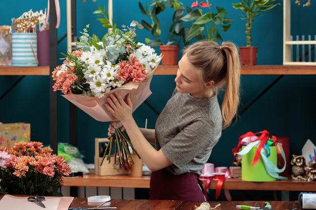 Kwiaciarnia składa bukiet. młoda, dorosła dziewczyna trzyma w rękach duży bukiet różnokolorowych chryzantem i sprawdza go.