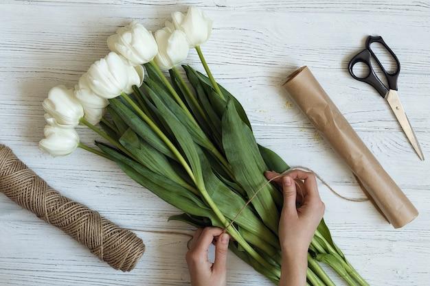 Kwiaciarnia składa bukiet z białych tulipanów