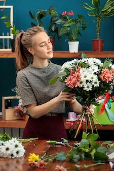 Kwiaciarnia składa bukiet z różnokolorowych chryzantem. młoda, dorosła dziewczyna pracuje z entuzjazmem.