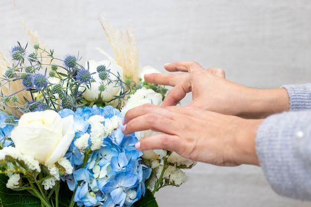 Kwiaciarnia śliczna kobieta robi bukiet białych róż i hortensji