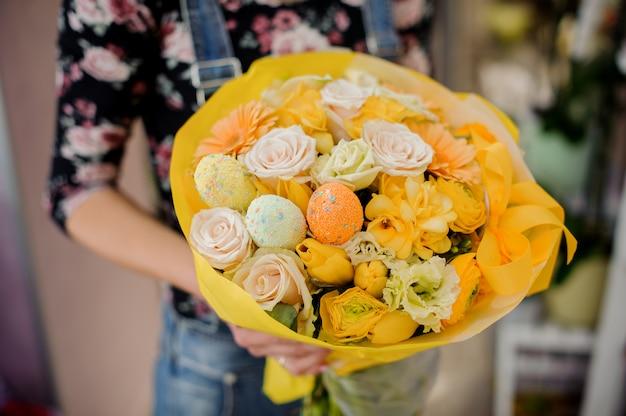 Kwiaciarnia trzyma jasny wielkanocny bukiet kwiatów