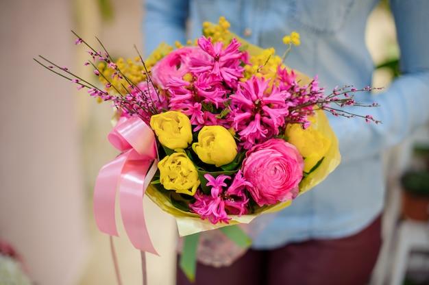 Kwiaciarnia trzyma piękny jasny różowy i żółty bukiet kwiatów