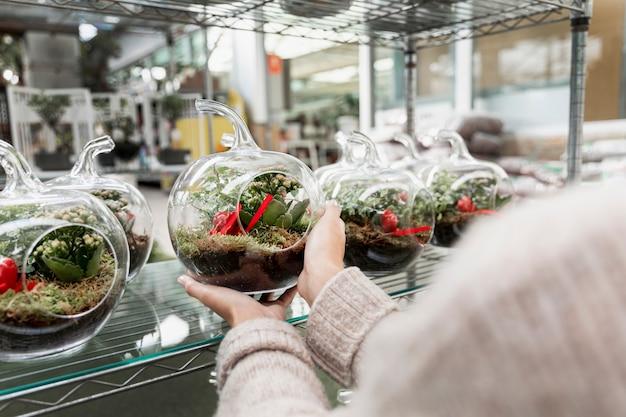 Kwiaciarnia trzyma przezroczysty wazon w kształcie kuli ziemskiej