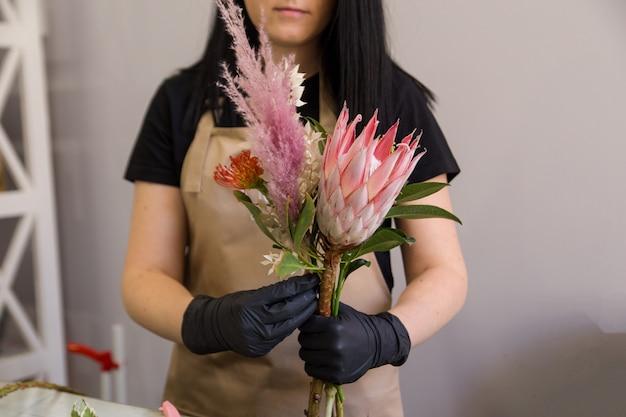 Kwiaciarnia w fartuchu z piasku w pracy tworzy bukiet proteas