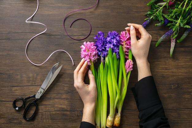 Kwiaciarnia w pracy kobieta dokonywanie moda nowoczesny bukiet różnych kwiatów na podłoże drewniane