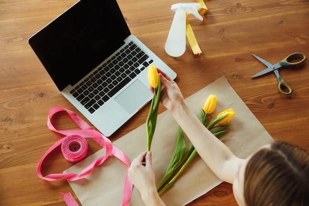 Kwiaciarnia w pracy: kobieta pokazuje jak zrobić bukiet z tulipanów. młoda kobieta kaukaski daje warsztaty online robienia prezentów, prezentów do świętowania. praca w domu, podczas gdy koncepcja izolacji, kwarantanny.