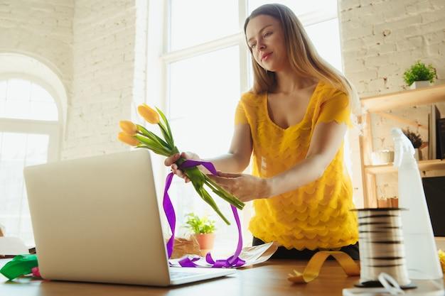 Kwiaciarnia w pracy: kobieta pokazuje jak zrobić bukiet z tulipanów.