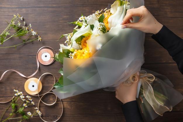 Kwiaciarnia w pracy: kobieta robi modny nowoczesny bukiet różnych kwiatów na drewnianej powierzchni.