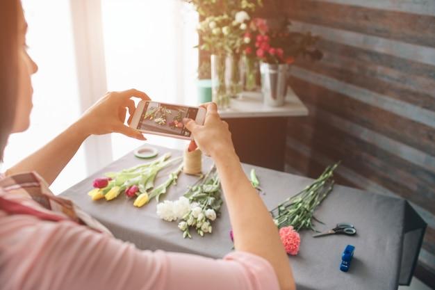 Kwiaciarnia w pracy: ładna młoda ciemnowłosa kobieta robi moda nowoczesny bukiet różnych kwiatów. kobiety pracujące z kwiatami w warsztacie. ona fotografuje kwiaty na smartfonie.