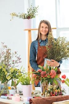 Kwiaciarnia w pracy młoda dziewczyna robi modny nowoczesny bukiet różnych kwiatów