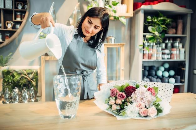 Kwiaciarnia wlewa wodę do wazonu w butiku z kwiatami. usługi florystyczne, kwiaciarnia, kwiaciarnia
