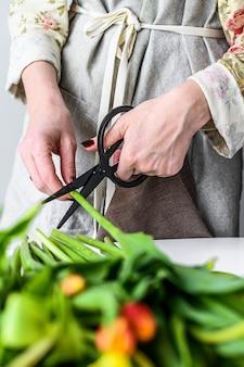 Kwiaciarnia z nożyczkami w dłoniach robi bukiet żółtych, pomarańczowych i czerwonych tulipanów.