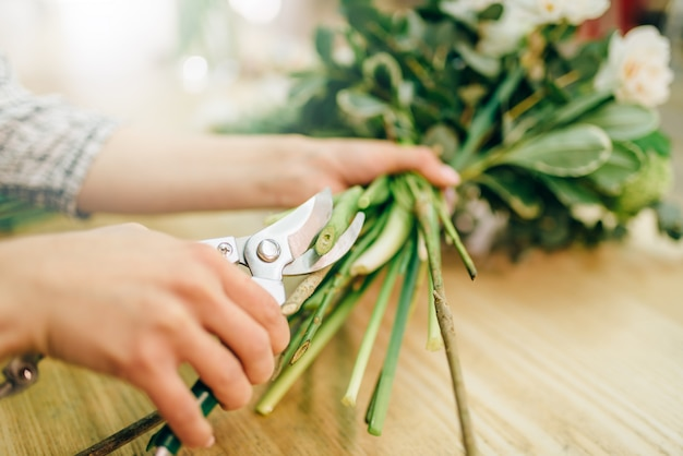 Kwiaciarnia zawiązuje wstążkę na bukiet kwiatów