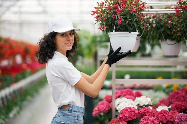 Kwiaciarnia żeńska trzyma doniczkę z kwitnącym kwiatem
