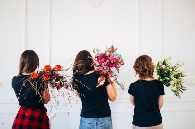 Kwiaciarnie dla dziewcząt z bukietami kwiatów. trzy dziewczyny w czarnych t-shirtach