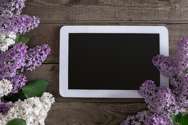 Kwiat bzu na rustykalnym drewnianym tle, tablet z pustym miejscem na wiadomość powitalną. widok z góry. koncepcja tło wiosna.