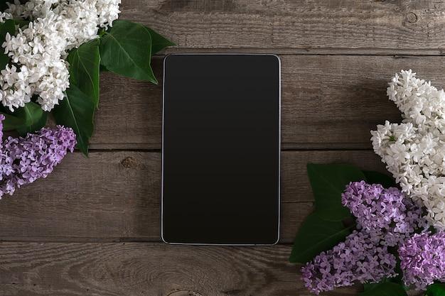 Kwiat bzu na rustykalnym drewnianym tle tabletu z pustą przestrzenią na powitanie wiadomości widok z góry