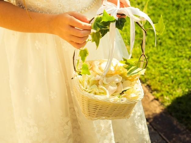 Kwiat dziewczyna w biel sukni z koszem płatki