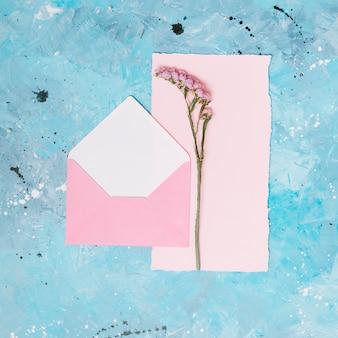 Kwiat gałąź z otwartą kopertą na błękita stole