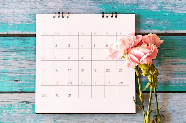 Kwiat goździka i kalendarz na tle drewna, walentynki, dzień matki lub tło urodziny