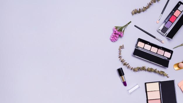 Kwiat i gałązki z pomadkami; pędzel do makijażu; szminka; kompaktowy proszek i paleta cieni do powiek na fioletowym tle