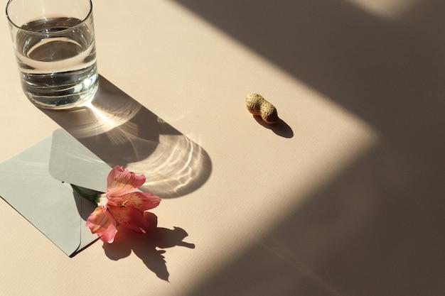 Kwiat, koperta, woda, orzeszki ziemne na stole z cieniem