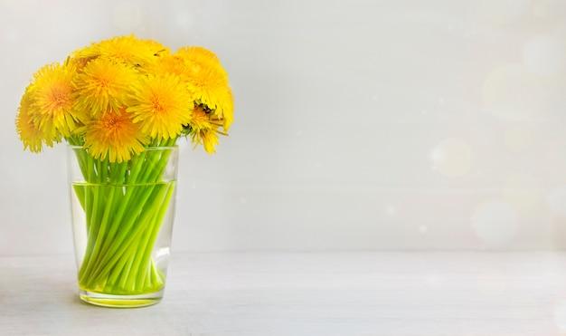 Kwiat mniszka lekarskiego w pełnym rozkwicie w szklance na drewnianym stole zdjęcie z bliska jako naturalne tło kwiat streszczenie tekstura transparent z miejsca na kopię