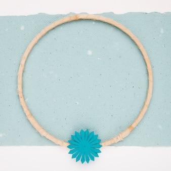 Kwiat na drewnianej okrągłej ramie na niebieskim papierze
