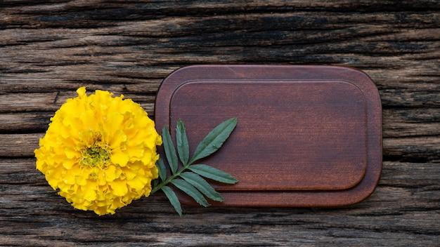 Kwiat nagietka wklejony na starym drewnianym tle.
