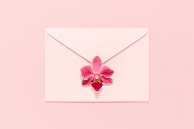 Kwiat orchidei na różowej kopercie. karta gratulacyjna, dzień kobiet, dzień matki, walentynki, urodziny.