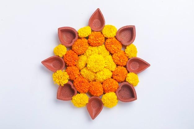 Kwiat rangoli na diwali festival wykonany przy użyciu nagietka i liści oraz lampy naftowej na białym tle