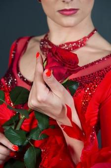Kwiat róży w kobiecej dłoni na czerwonej sukience. miłość, pożądanie, romans. florystyka, wystrój, design, kwiaciarnia. dzień kobiet, 8 marca, wiosna. urodziny, rocznica, obchody świąt.