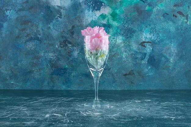 Kwiat w małej szklance, na białym tle.
