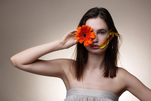 Kwiat w pobliżu oka. ciemnowłosa modelka w sukience z odkrytymi ramionami trzyma pomarańczowy kwiat przy oku