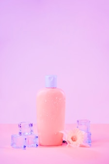 Kwiat z kryształowymi kostkami lodu z butelką z filtrem przeciwsłonecznym na różowym tle