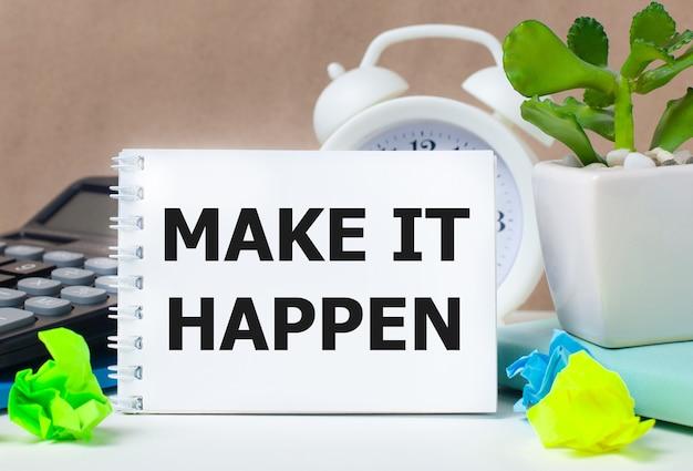 Kwiatek w doniczce, kalkulator, biały budzik, różnokolorowe karteczki i biały notes z napisem make it happen na pulpicie.