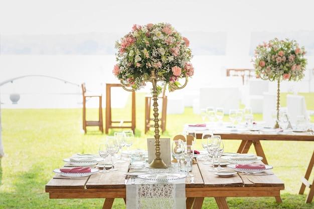 Kwiatowa aranżacja na drewnianym stole z kryształami ustawiona w ogrodzie na imprezę towarzyską w meksyku