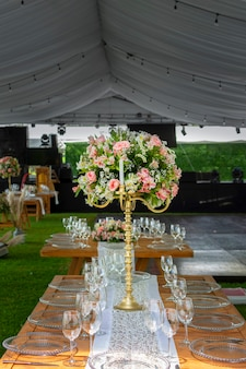 Kwiatowa aranżacja na drewnianym stole ze szklanymi naczyniami ustawionymi w ogrodzie na imprezę towarzyską w meksyku