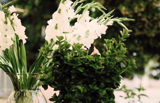 Kwiatowa dekoracja ślubna w restauracji na świeżym powietrzu latem