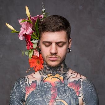 Kwiatowa dekoracja za wytatuowanym i przebitym młodym mężczyzną na szarym tle