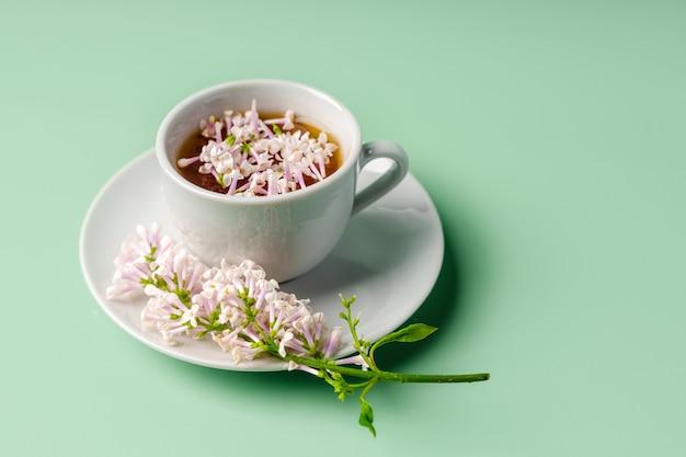 Kwiatowa kompozycja wiosenna i kubek herbaty na zielonym tle widok z góry miejsca kopiowania copy