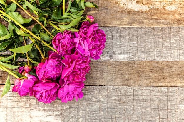 Kwiatowa ramka z bukietem świeżych kwiatów kwitnących różowej piwonii magenta na starym odrapanym rustykalnym drewnianym tle, lato