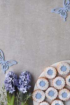 Kwiatowe ciasteczka linzer z niebieskimi szkliwami na jasnym betonie ozdobione niebieskimi kwiatami hiacyntu i motylami