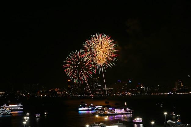 Kwiatowe fajerwerki na plaży i odbicie koloru na powierzchni wody w świetle miasta