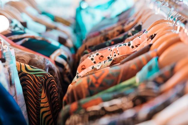 Kwiatowe koszule wiszące na drewnianym wieszaku wiszącym na szynie