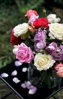 Kwiatowy bukiet różnych różnokolorowych róż w szklanym wazonie na ciemnym stole z opadłymi płatkami